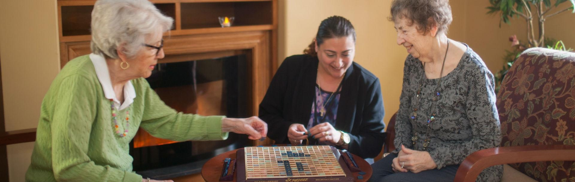 Our long term residents playing scrabble with staff